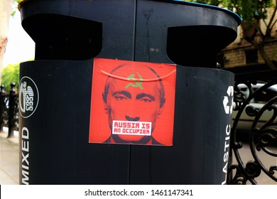 "Tbilisi, Georgia. July 2019. Even if peaceful, the demonstration against Putin continue. This sticker is glued on a garbage can of Tbilisi. The face of Putin with the written "" Russia is an occupier """