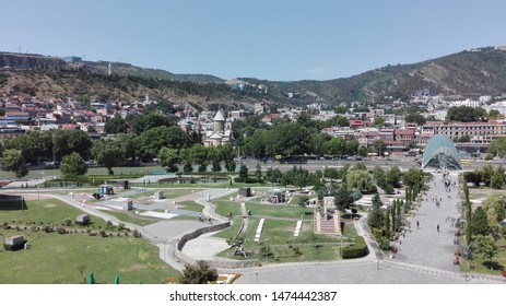 Tbilisi, Georgia. July 2019. Panoramic aerial view of the Tbilisi city centre from the Rike park, with the Peace Bridge and the Kura riverside.