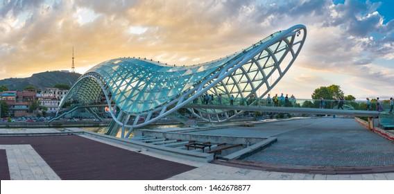 Tbilisi, Georgia - July 25 2019: Bridge of Peace in Tbilisi. Pedestrian bridge of steel and glass in Rike Park. Panorama view.