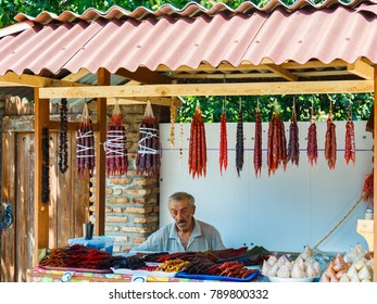 TBILISI, GEORGIA - JULY 27, 2017: Georgian man sells chestnuts and local dessert of churchkhela.