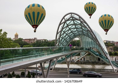 Tbilisi, Georgia - June 14, 2019: Hot air balloons and tourist landmark - glass Bridge of Peace in Tbilisi.