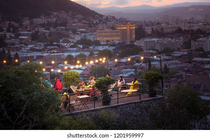 TBILISI, GEORGIA - JUNE 15, 2017: People are resting in a cafe on the terrace in the evening. Restaurant on the terrace. Chillout bar on the hill with a panoramic view of the evening Tbilisi city