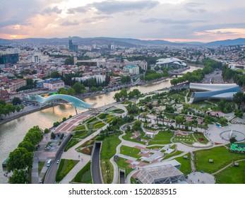 Tbilisi, Georgia - June 2018: Rike Park, Kura River and Peace Bridge at sunset, aerial view