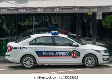 Tbilisi, Georgia - June 27 2019: Police car on an asphalt road against the mountains on a sunny clear day