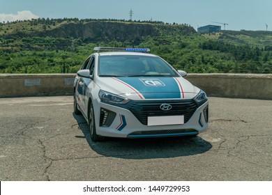 Tbilisi, Georgia - June 28 2019: Police car on an asphalt road against the mountains on a sunny clear day