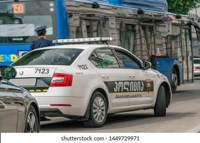 Tbilisi, Georgia - June 28 2019: Police car on the asphalt road in the city on a sunny clear day, policeman near the car