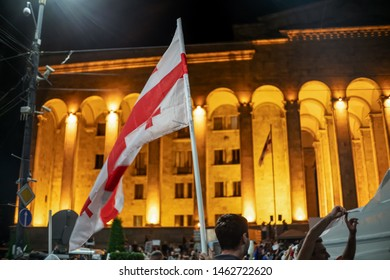 Tbilisi, Georgia - June 29 2019: Georgian flag on the background of the parliament in Tbilisi at night during the rally