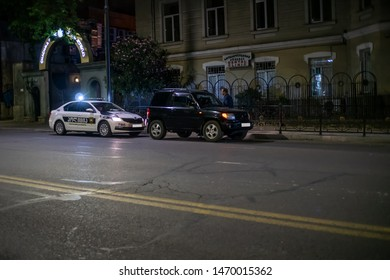 Tbilisi, Georgia - June 29 2019: A police officer stopped a car to check documents, clarify the circumstances of a black car. Polish car on the road to Tbilisi at night
