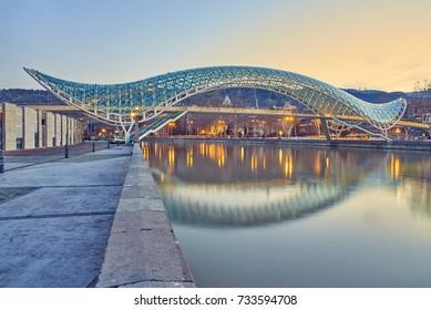 TBILISI, GEORGIA - MARCH 5, 2016: The Bridge of Peace is a bow-shaped pedestrian bridge over the Kura River in Tbilisi, capital of Georgia.