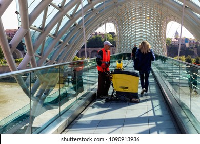 Tbilisi, Georgia - May 1, 2018: Worker cleaning the pedestrian bridge with professional floor cleaning machine