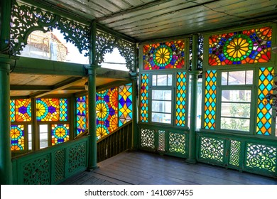 Tbilisi / Georgia - May 16 , 2019 : Colorful stained glass window. Old house with wood balcony in the old town of Tbilisi, Georgia.