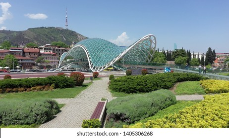 Tbilisi, Georgia - May 8, 2019: The Bridge of Peace is a bow-shaped pedestrian bridge, over the Kura River in downtown Tbilisi, capital of Georgia. Aerial view