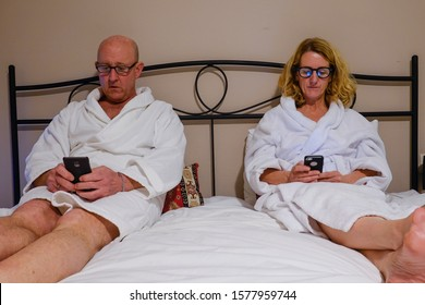 Tbilisi, Georgia A middle aged couple in bed with white bathrobes reading their phones.