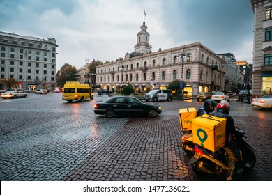 Tbilisi, Georgia - November 22, 2018:  Two Parked Glovo's Courier At Freedom Square, Tbilisi On Background The Tbilisi City Assembly. Tbilisi Sakrebulo.