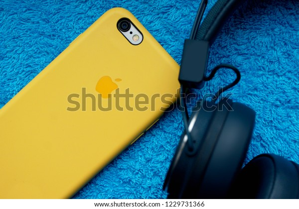 Tbilisi / Georgia - November 24, 2018: iPhone in a yellow case next to black headphones on a blue textile surface