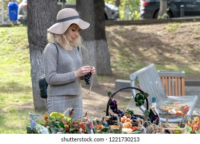 TBILISI, GEORGIA - NOVEMBER 4, 2018: a female stallholder prepares her artisan  items for sale at an open-air event in the city.