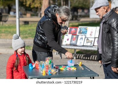 TBILISI, GEORGIA - NOVEMBER 4, 2018: a vendor looks on as a customer buys a toy for a small girl at an open-air event in the city