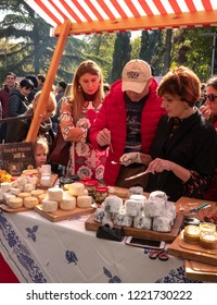 TBILISI, GEORGIA - NOVEMBER 4, 2018: a stallholder providing samples of cheese to a customer at an open-air wine and chese festival