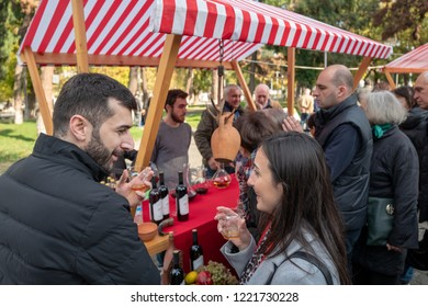TBILISI, GEORGIA - NOVEMBER 4, 2018: a man and a woman smile as they try samples of wine at an open-air cheese and wine festival