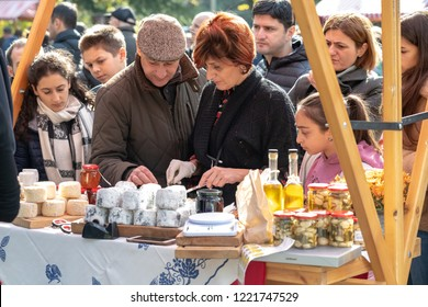 TBILISI, GEORGIA - NOVEMBER 4, 2018: a stallholder provides cheese samples to a customer as two girls look on.