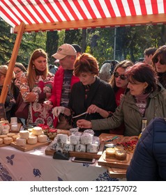 TBILISI, GEORGIA - NOVEMBER 4, 2018: a woman reaches for a sample of cheese at an open-air wine and cheese festival in the city.