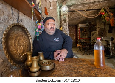 TBILISI, GEORGIA - OCT 16: Elderly man with bottle of homemade white wine sitting in wine bar at historical stone cellar on October 16, 2016. Tbilisi has a population of 1.5 million people