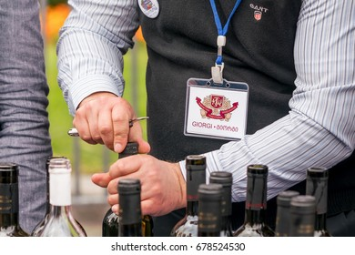 TBILISI, GEORGIA, October 15, 2016: Man opens a bottle of wine
