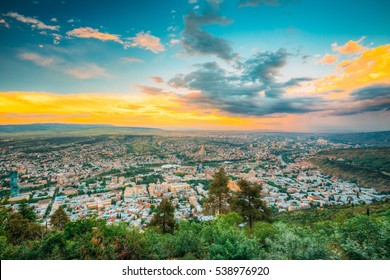 Tbilisi, Georgia. The Scenic Aerial Panoramic Cityscape With Beautiful Dramatic Yellow Sunset, Sunrise On Blue Cloudy Summer Sky.