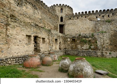 Tbilisi, Georgia-May,6 2019: Courtyard of Svetitskhoveli Cathedral. Part fortress wall with watchtower and old kvevri vessels