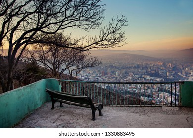 Tbilisi Historic Old Town Houses Panorama View Geargia capital with evening sunset light, bench and tree