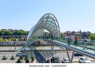 TBILISI - MAY 3: Tourists enjoy the sunny weather and walk through the futuristic Bridge of Peace over the Kura River on 3 May 2018 in Tbilisi, Georgia.