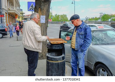 Tbilisi,Georgia,April 2018.Two elderly  men taxi- drivers playing backgammon  in the street waiting passengers.Backgammon is one of the famous and oldest board games for two players in the world