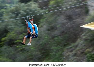 TBLISI, GEORGIA, JUNE 15: Tourists enjoying Zip-line ride from Narikala Fortress hilltop to botanical park downhill on June 15, 2018, Tblisi, Georgia