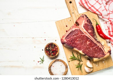 T-bone beef steak on white wooden table with spices. Ready for cooking. Top view with copy space.