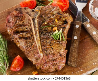 T-Bone Steak with Herbs on  a rustic wooden table