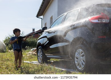 Tchaykovskiy, Perm region / Russia - August 12 2018:  the child washes the car. car washing with water under pressure
