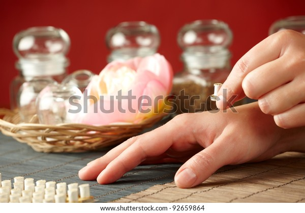 TCM Traditional Chinese Medicine. Hand applying mini moxa stick therapy, natural herbs in glass jars in background