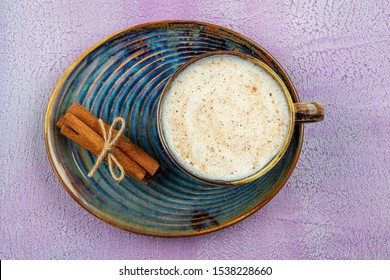 TCup of salep milky hot drink of Turkey with cinnamon powder and sticks healthy spice on black table. Sahlep background.