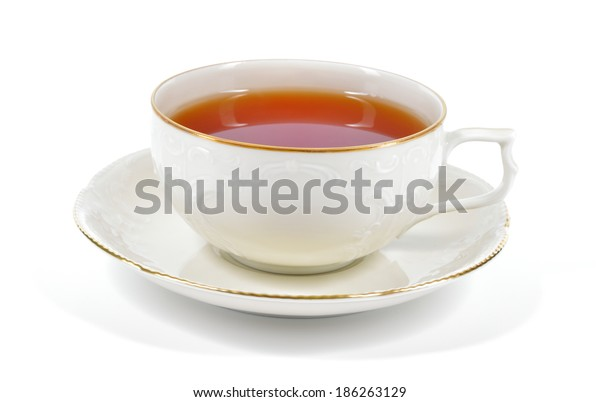 Tea in antique porcelain cup isolated on white background. Porcelain cup and saucer with delicate relief structures and gold decoration.