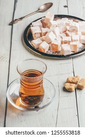 Tea in arabic glass with turkish delight Rahat Lokum over wooden surface