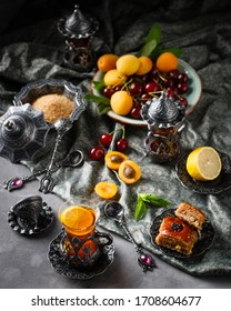 tea armud in Turkish style with lemon. served on a silk tablecloth with baklava and fruit-cherries and apricots. close up