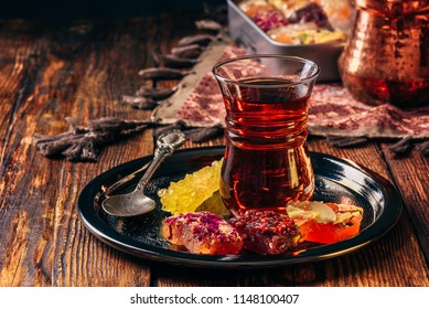 Tea in armudu glass with oriental delight rahat lokum on metal tray over wooden surface and tablecloth