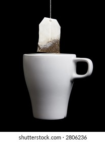 Tea bag being pulled out of a white teacup after steeping.