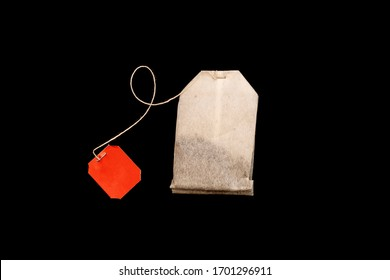 Tea bag with blank red label isolated on black background