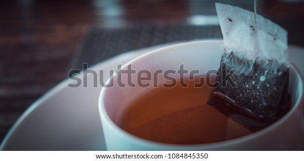 Tea bag in a glass of hot water. (vintage tone)