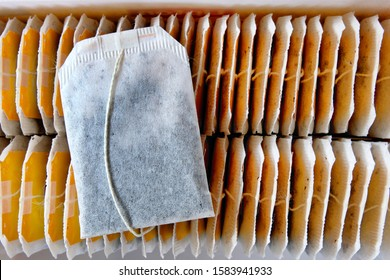 A tea bag lying on top of rows of other neatly arranged teabags inside a recently opened tea box. A choice selection of teabags for a morning drink and a refreshing afternoon break.