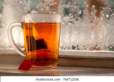 A tea bag in a mug. A mug of tea on the balcony window sill in winter cold. On the glass is a frost. Tea and frosty patterns. A cup of tea in winter against the background of snow.