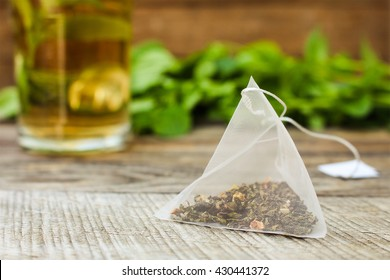 Tea bag on background of mint and and cup