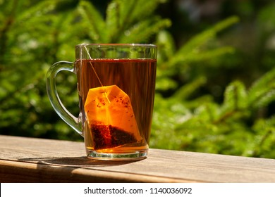 Tea and tea bag under the summer sun. A tea bag in a glass mug on the windowsill and against the background of green summer trees.