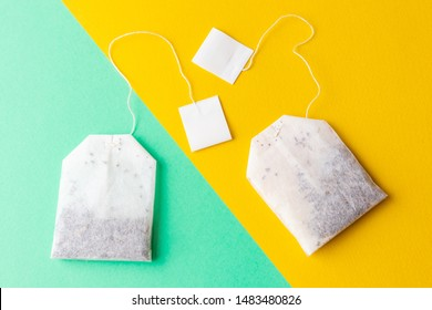 Tea bags with white labels on a pastel green and bright yellow background. Minimalism, flat lay, place for text.